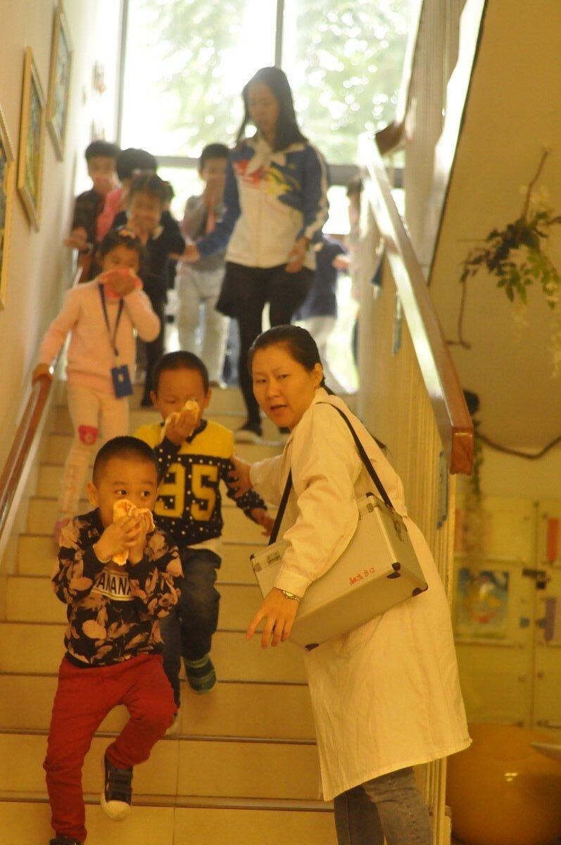 还是9:49分,中班小朋友已经撤离到一楼。医务室医生已经背上药箱一边在楼梯口接应小朋友,一边给小朋友指示逃生出口21.jpg